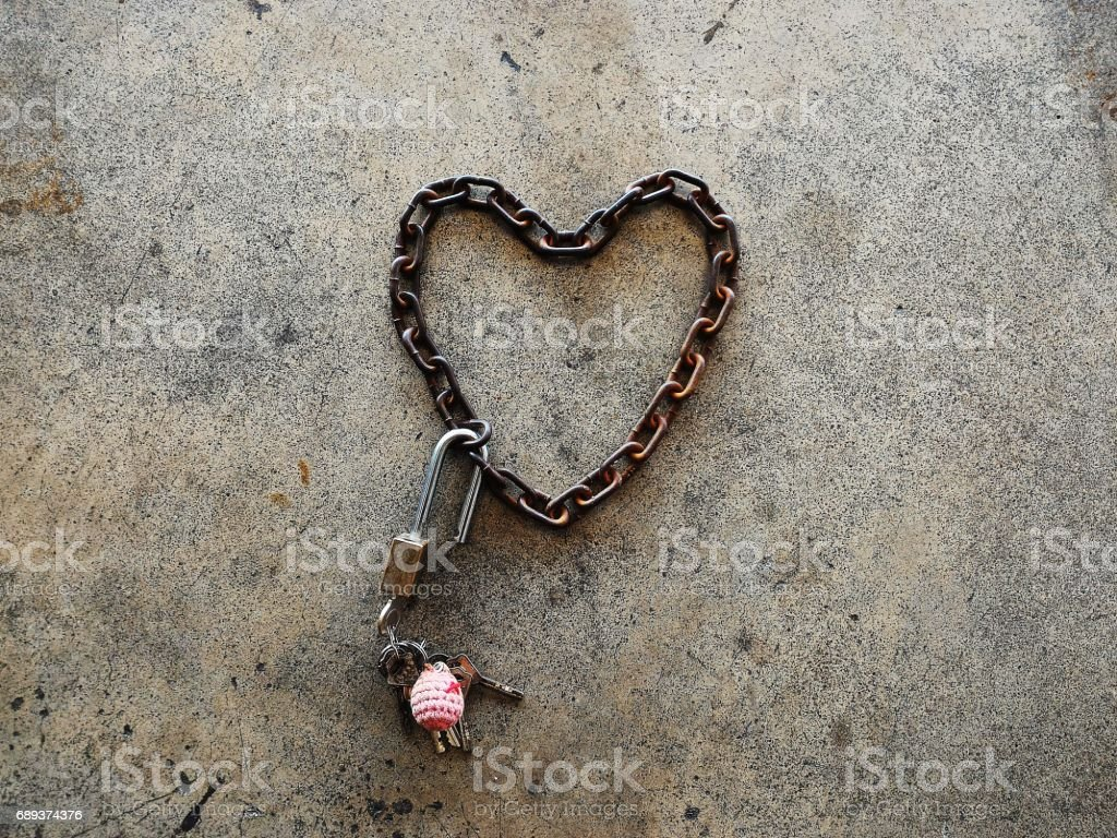 old chain heart-shaped with brass padlock and many key on cememt floor stock photo