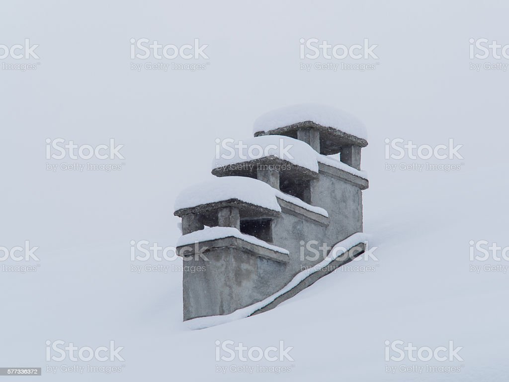 old chimneys covered by snow in winter during a snowfall stock photo