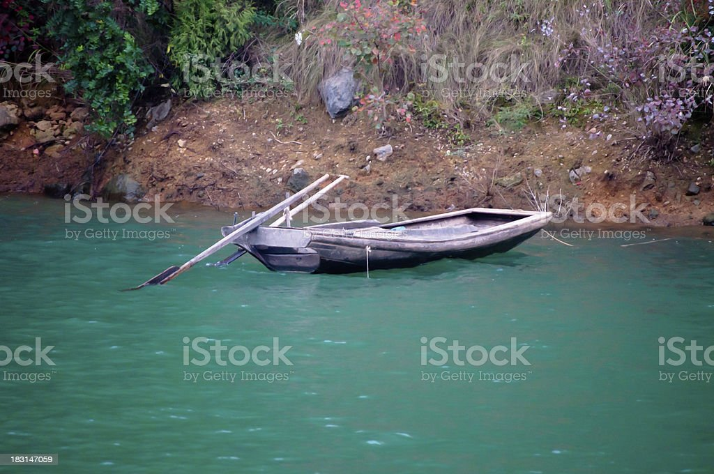 Old Chinese dhou and oars anchored in serene aqua waters royalty-free stock photo
