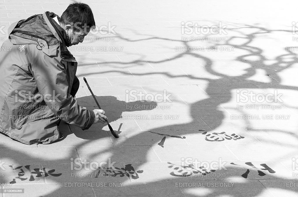 Old Chinese man writes poems sitting under tree in park stock photo