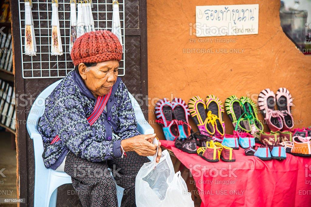 Old Chinese woman sell  Yunnan's shoes at Yunnan cultural villege stock photo