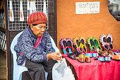 Old Chinese woman sell  Yunnan's shoes at Yunnan cultural villege