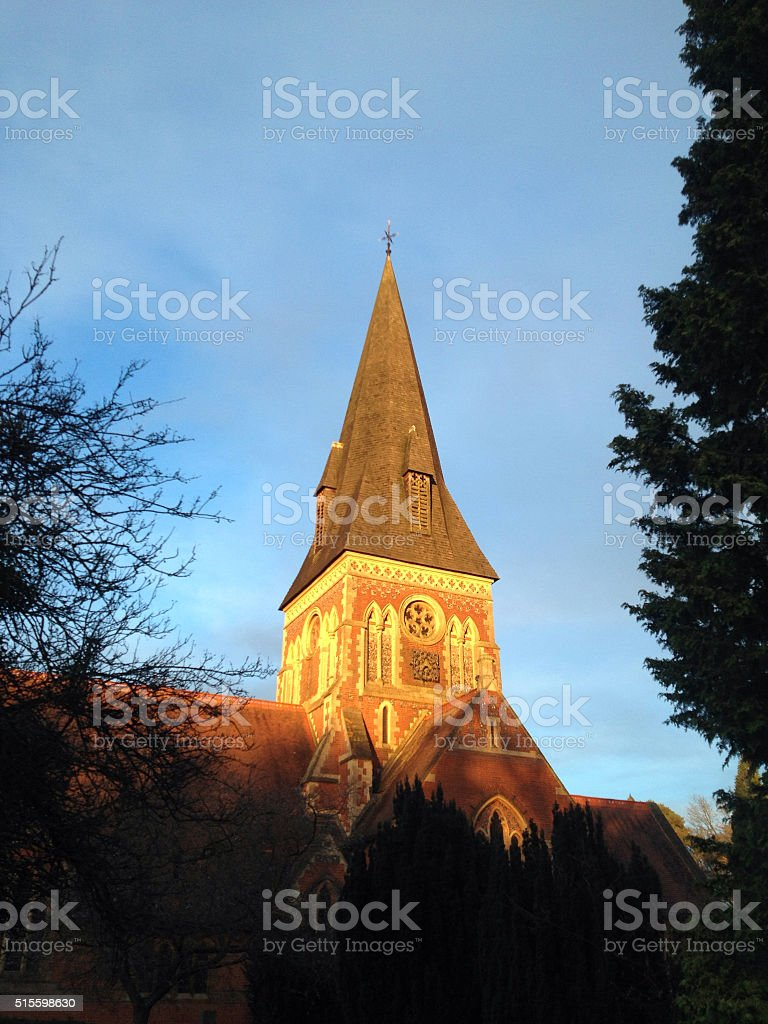 Old church spire in evening sun stock photo