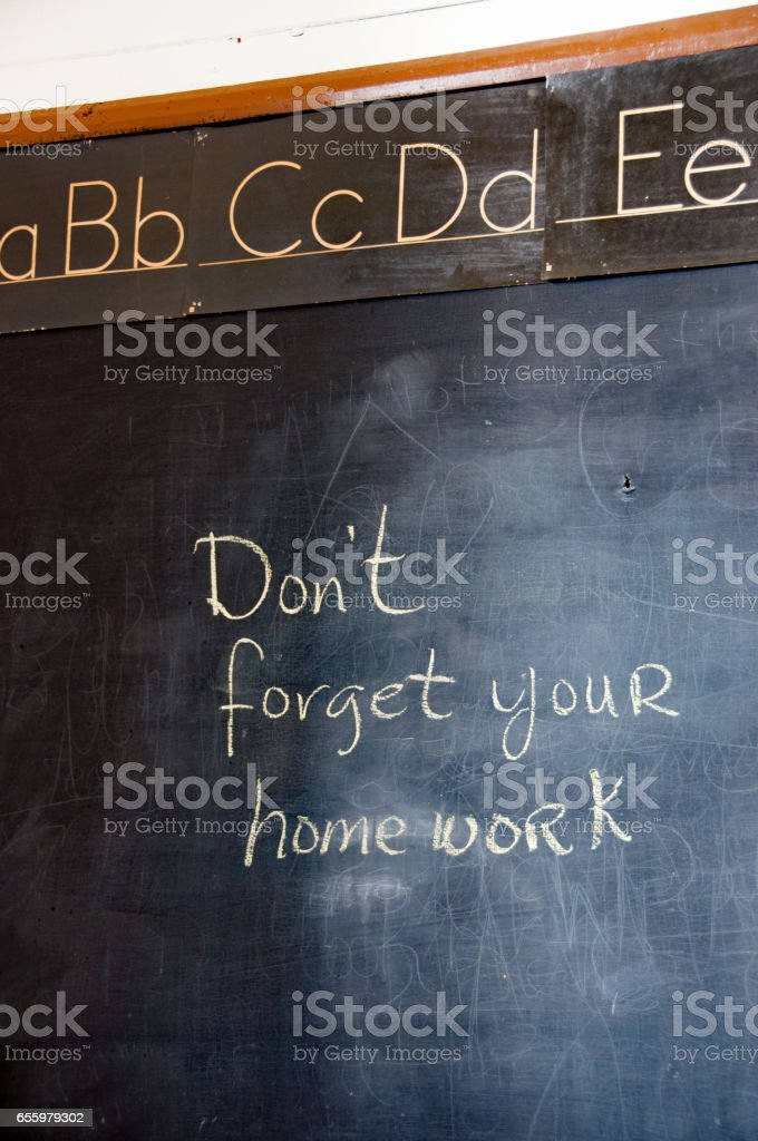 Old classroom blackboard with note on homework stock photo