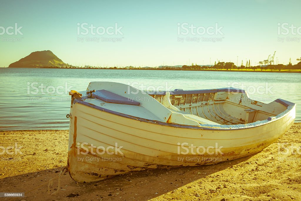 Old clinker design dinghy on beach stock photo