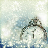 Old clock with fireworks and holiday lights