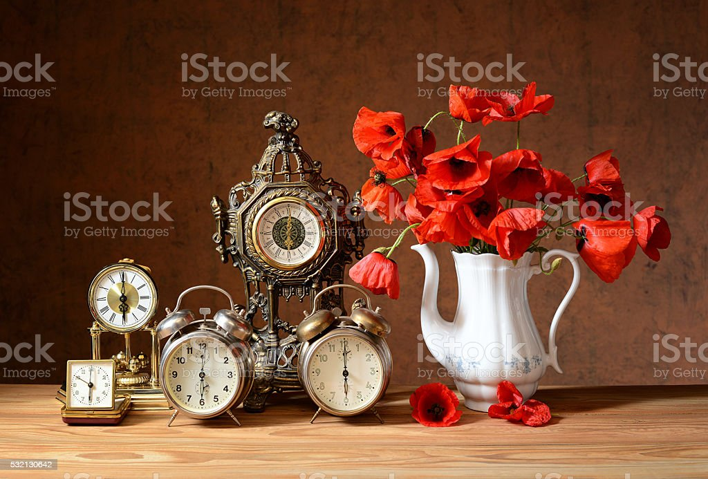 Old clocks and poppies in a vase stock photo