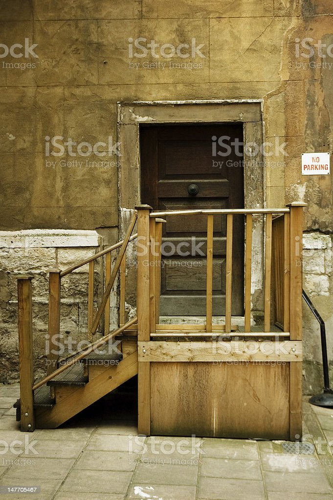 Old closed wooden door with broken bannister royalty-free stock photo