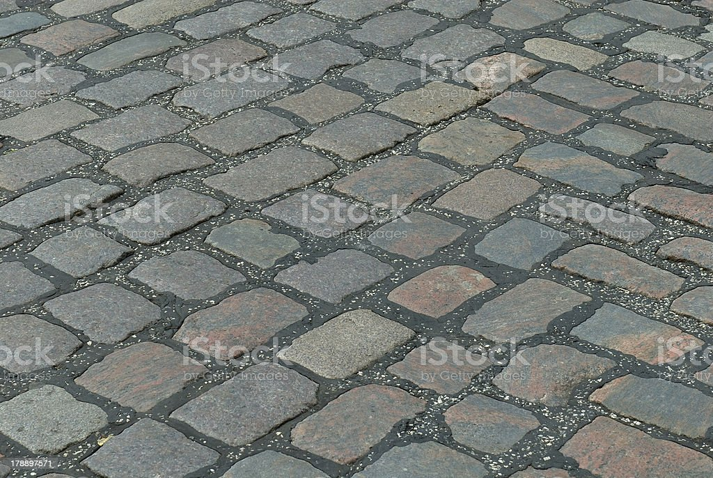Old cobbled stone road running diagonally. royalty-free stock photo
