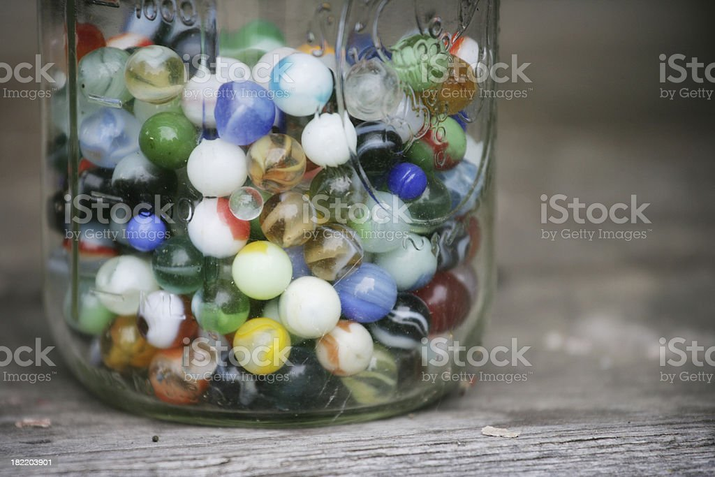 Old Colorful Marbles in a Glass Jar stock photo
