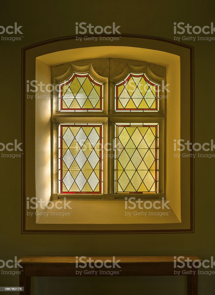 Old colorful stained glass window with diamond pattern stock photo