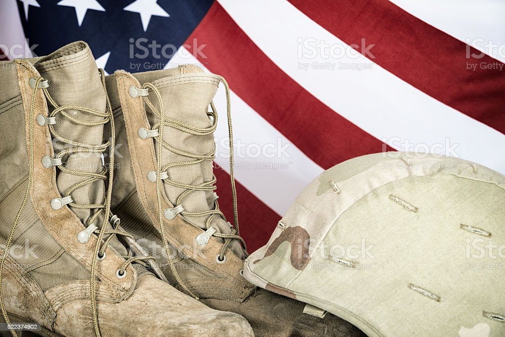 Old combat boots and helmet with American flag stock photo