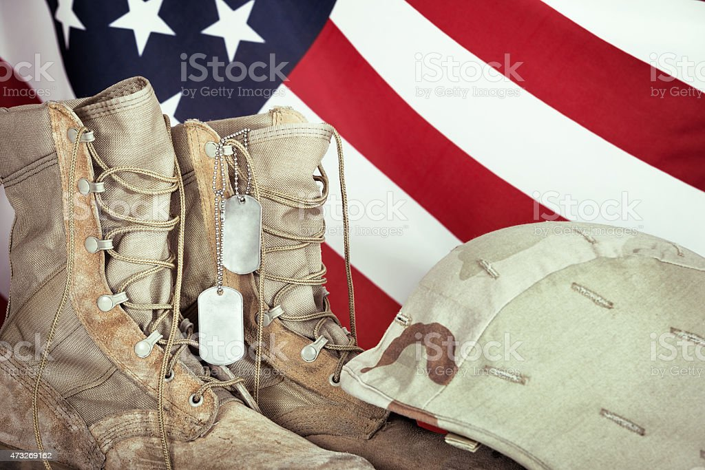 Old combat boots, dog tags, and helmet with American flag stock photo