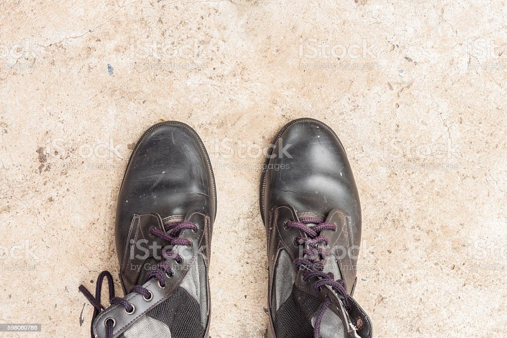 old combat boots on the cement floor stock photo