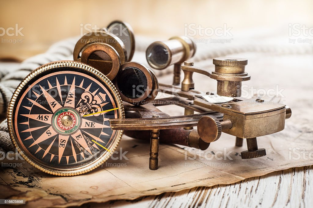 Old compass, astrolabe on vintage map. stock photo