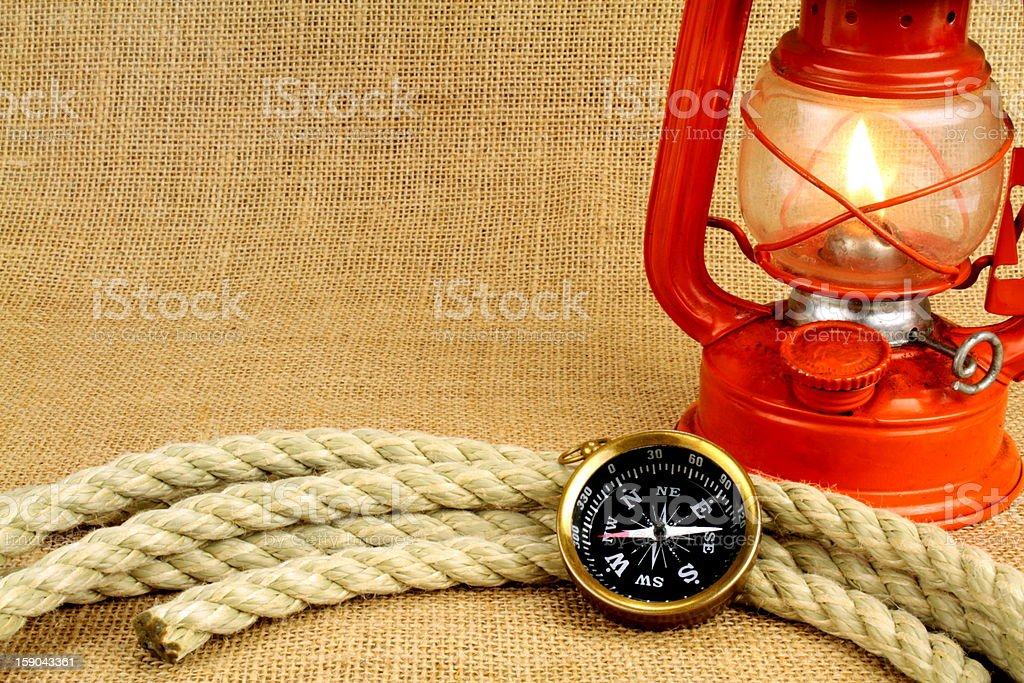 Old compass, oil lamp and rope on burlap stock photo