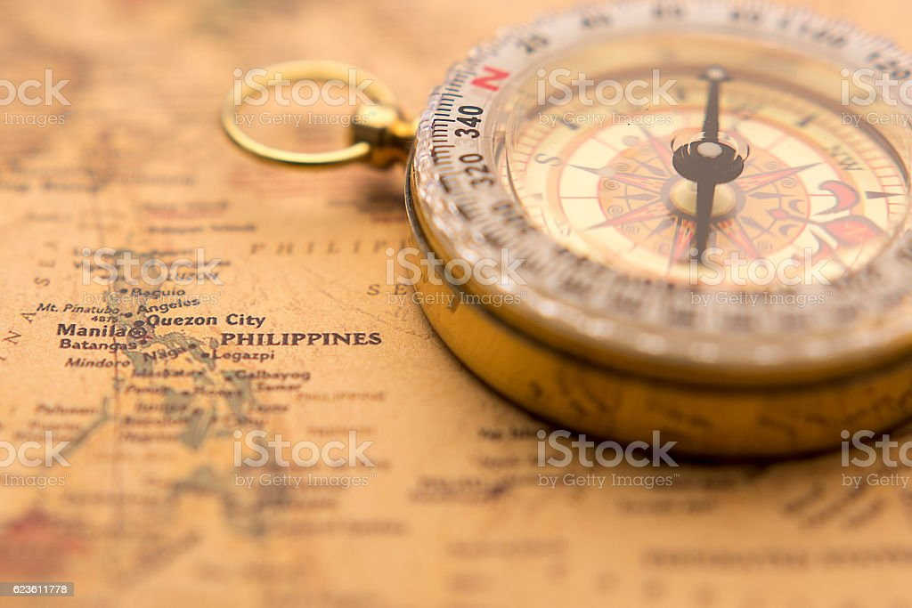 Old compass on vintage map selective focus on Philippines stock photo