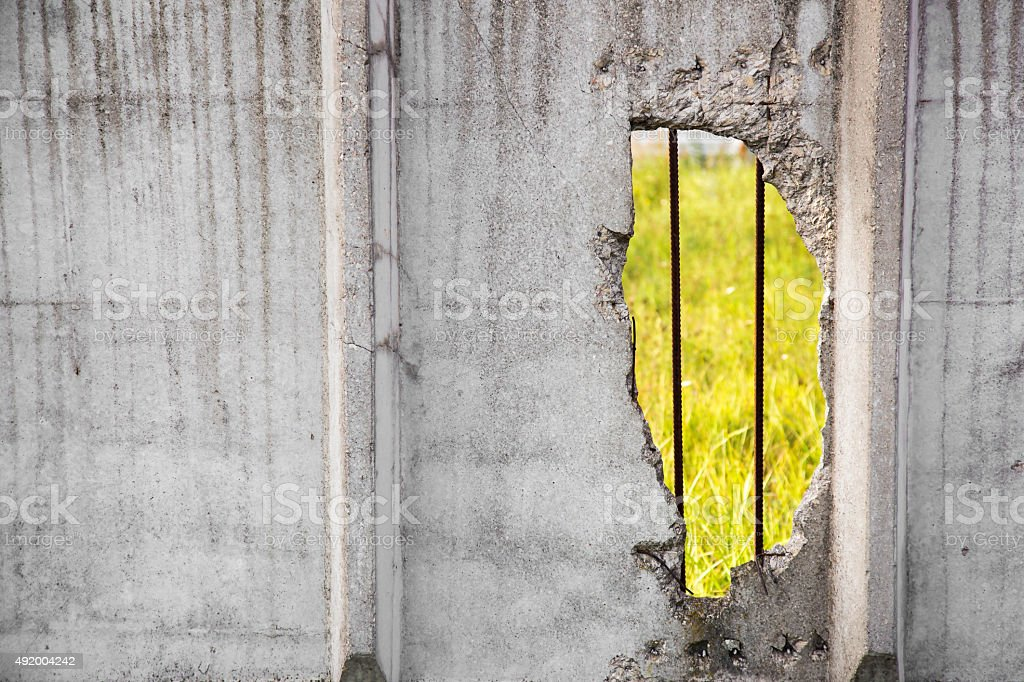 old concrete fence with big hole stock photo