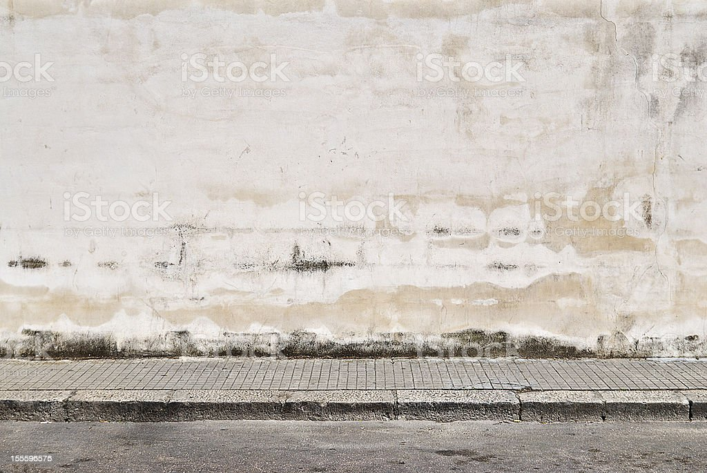Old concrete grunge wall with sidewalk stock photo
