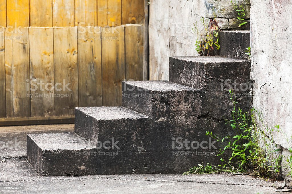 Old concrete stairs near wooden wall stock photo