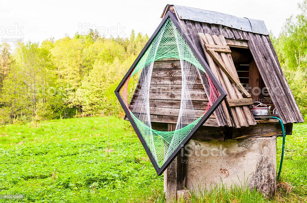 Old concrete well with wooden roof, metal kettle, psychedelic decoration. stock photo