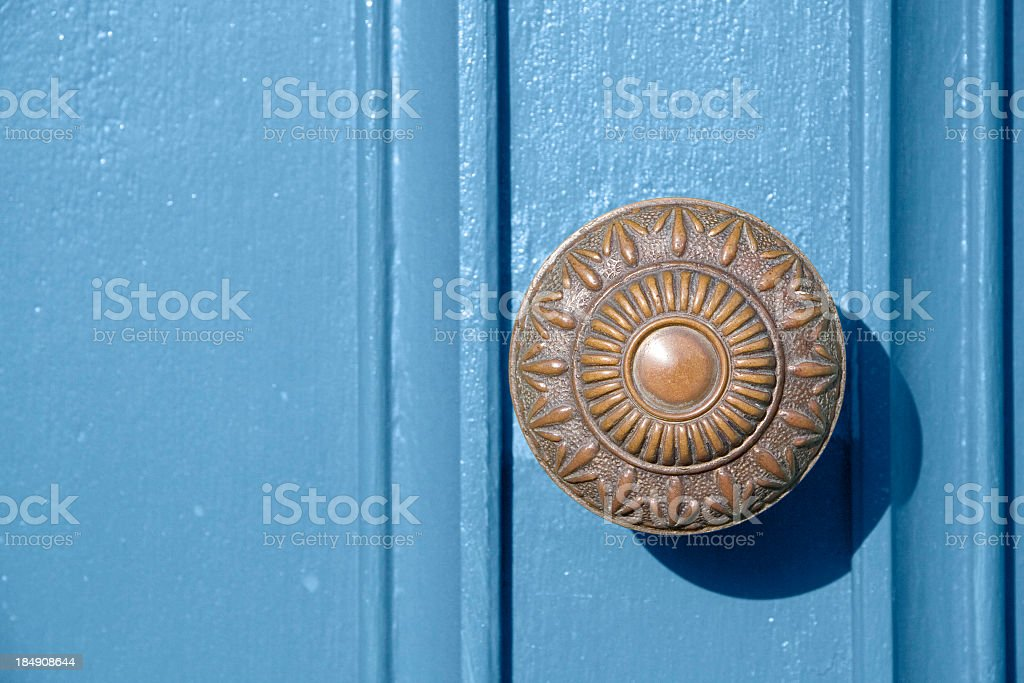 Old copper door knob on blue door stock photo