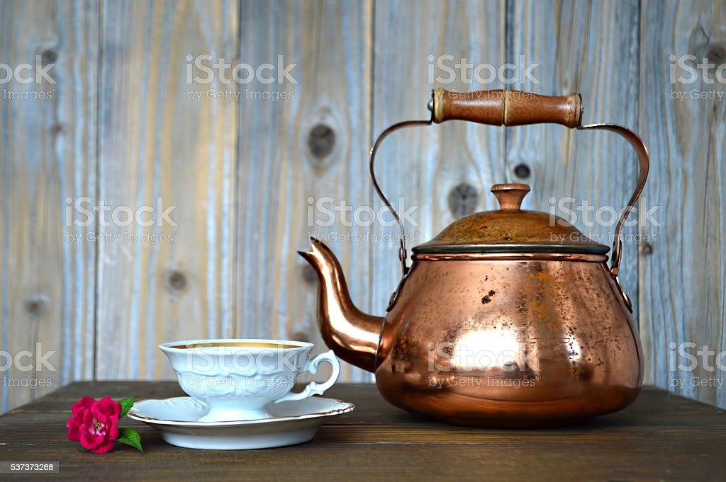 Old copper teapot and porcelain teacup stock photo