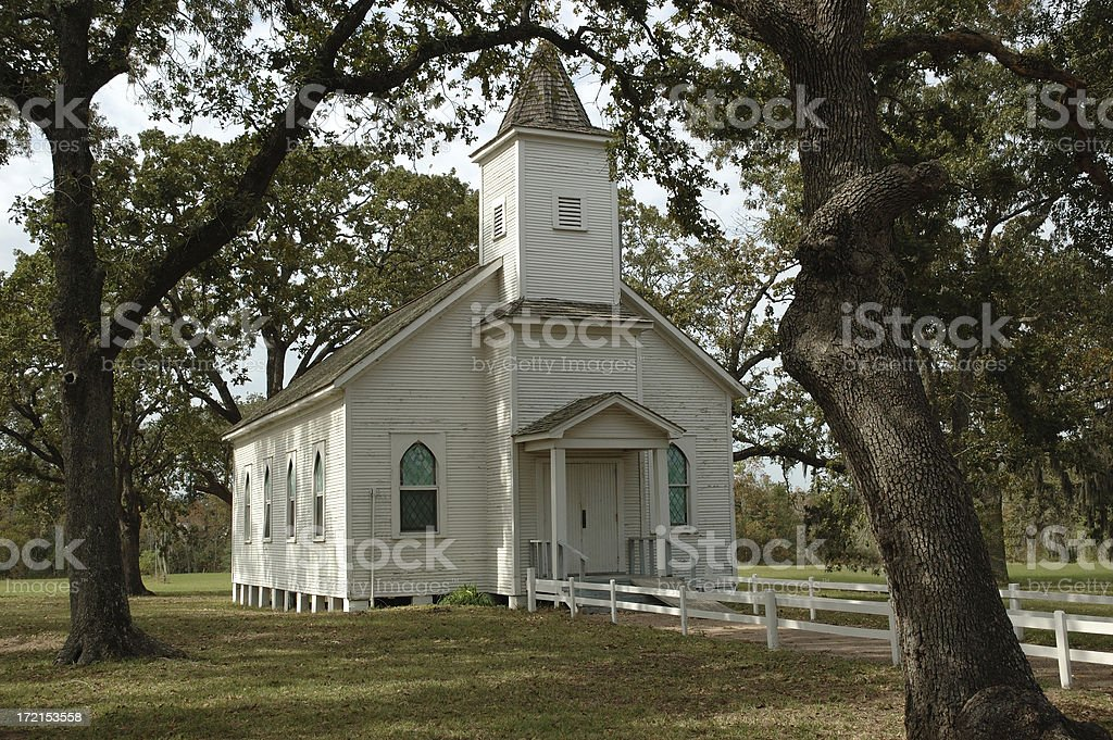 Old Country Church Framed By Two Large Oak Trees stock photo