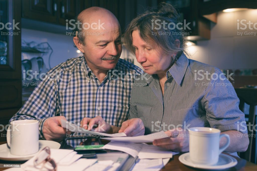 Old couple counting family money stock photo