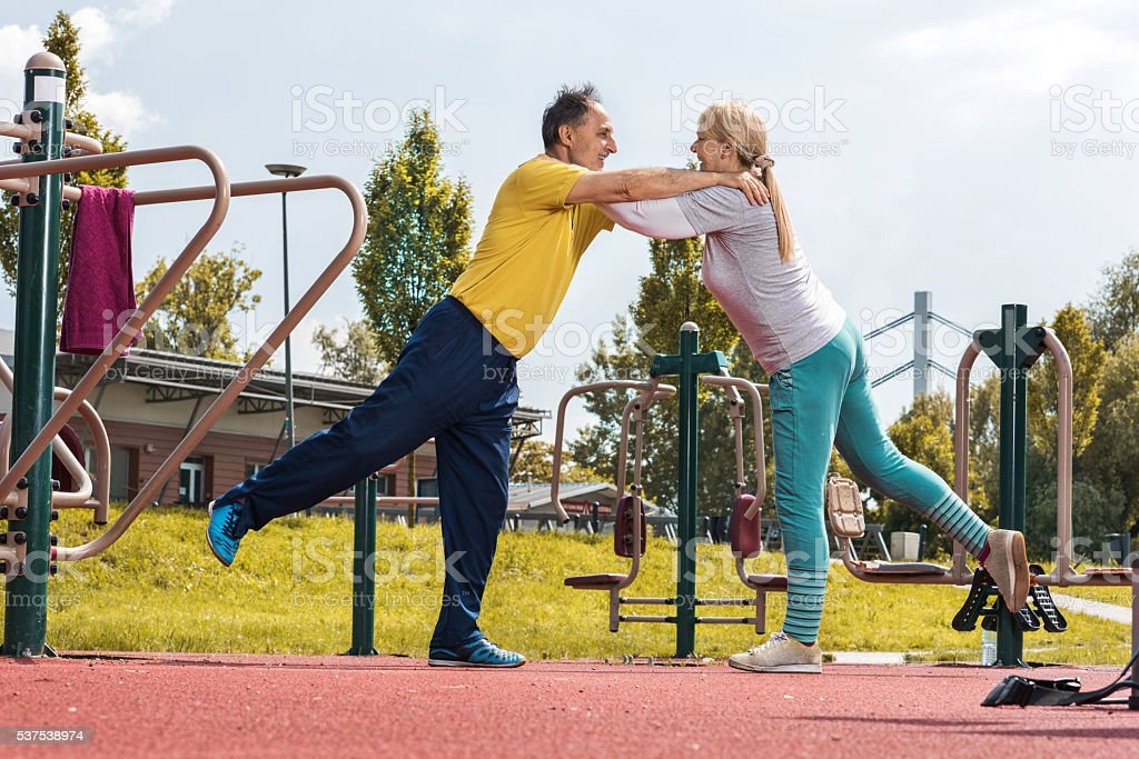 Old couple doing balance exercises while holding to each other. stock photo