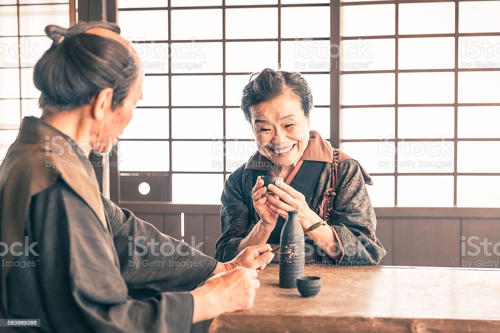 Old couple drinking sake in a traditional japanese house stock photo