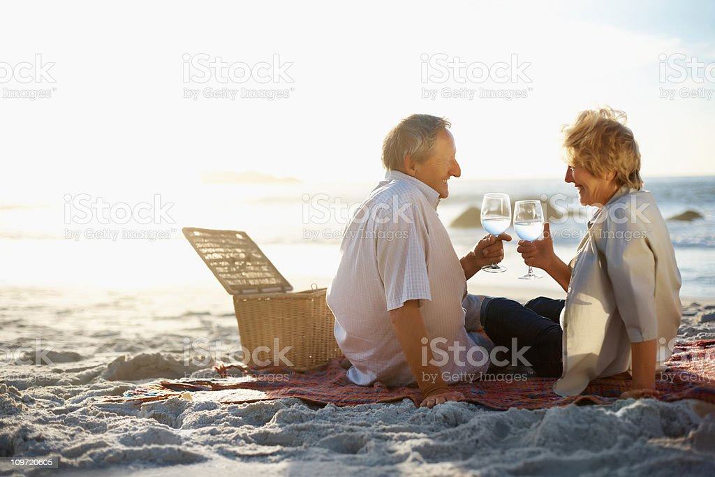 Old couple enjoying their vacation by toasting wine glasses royalty-free stock photo