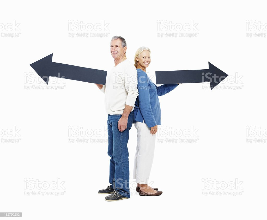 Old couple holding arrow signs in the opposite directions royalty-free stock photo