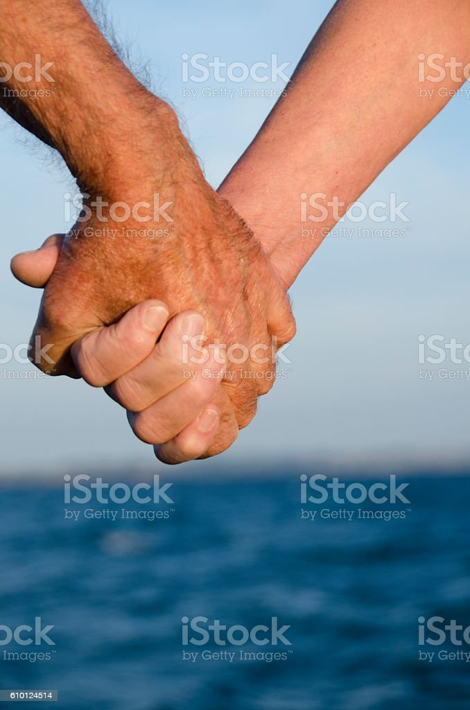 Old couple holding hands after bathing in the sea stock photo