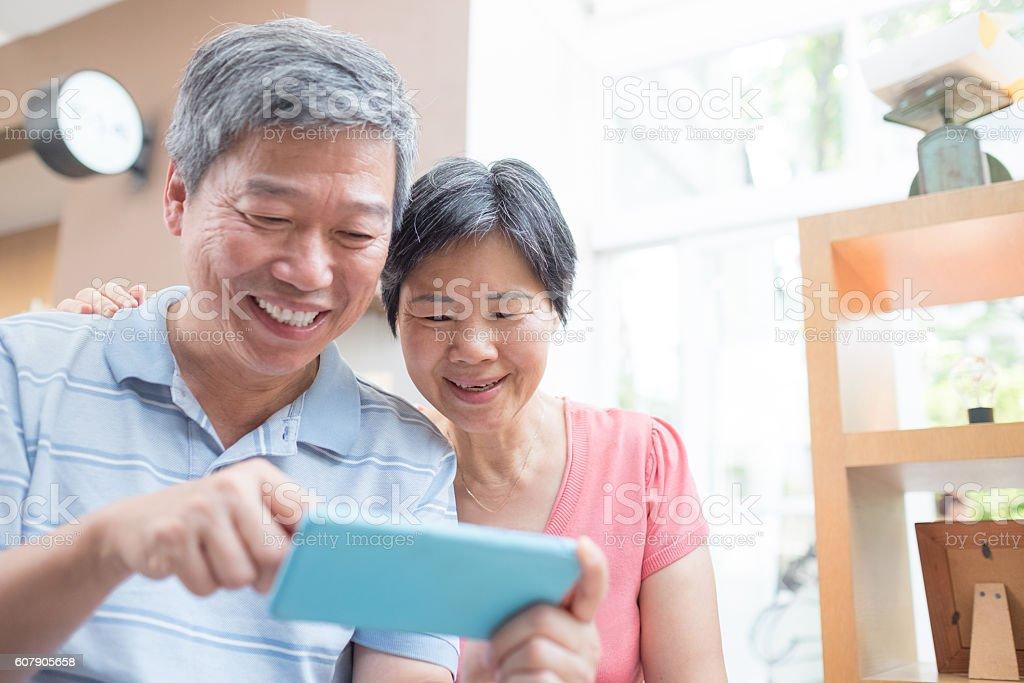 old couple look smaprt phone stock photo