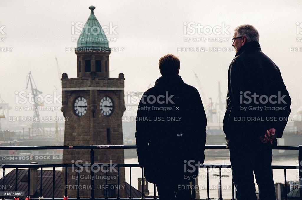 Old couple looking at Landungsbruecken in Hamburg, Germany stock photo