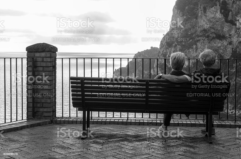 Old Couple Sitting on a Park Bench Watching Sunset stock photo
