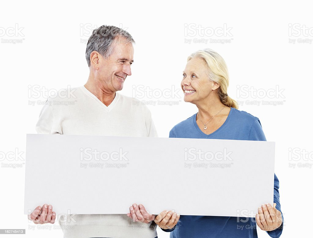 Old couple with a blank signboard looking at eachother royalty-free stock photo