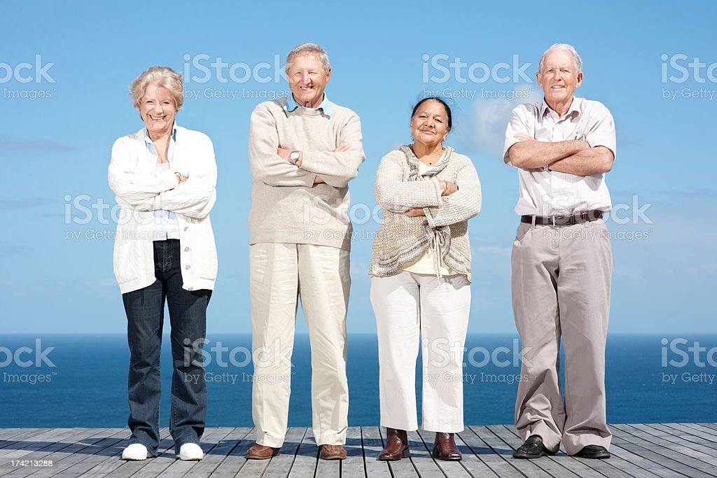 Old couples standing with folded hands on the wooden plank stock photo
