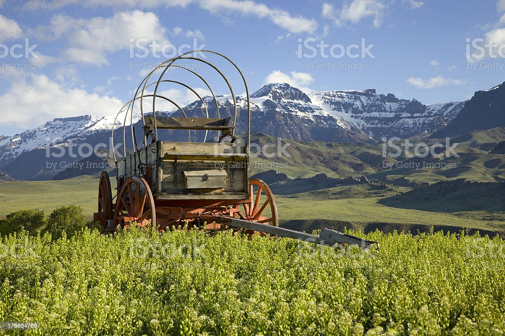 Old covered wagon with mountain backdrop in Wyoming royalty-free stock photo