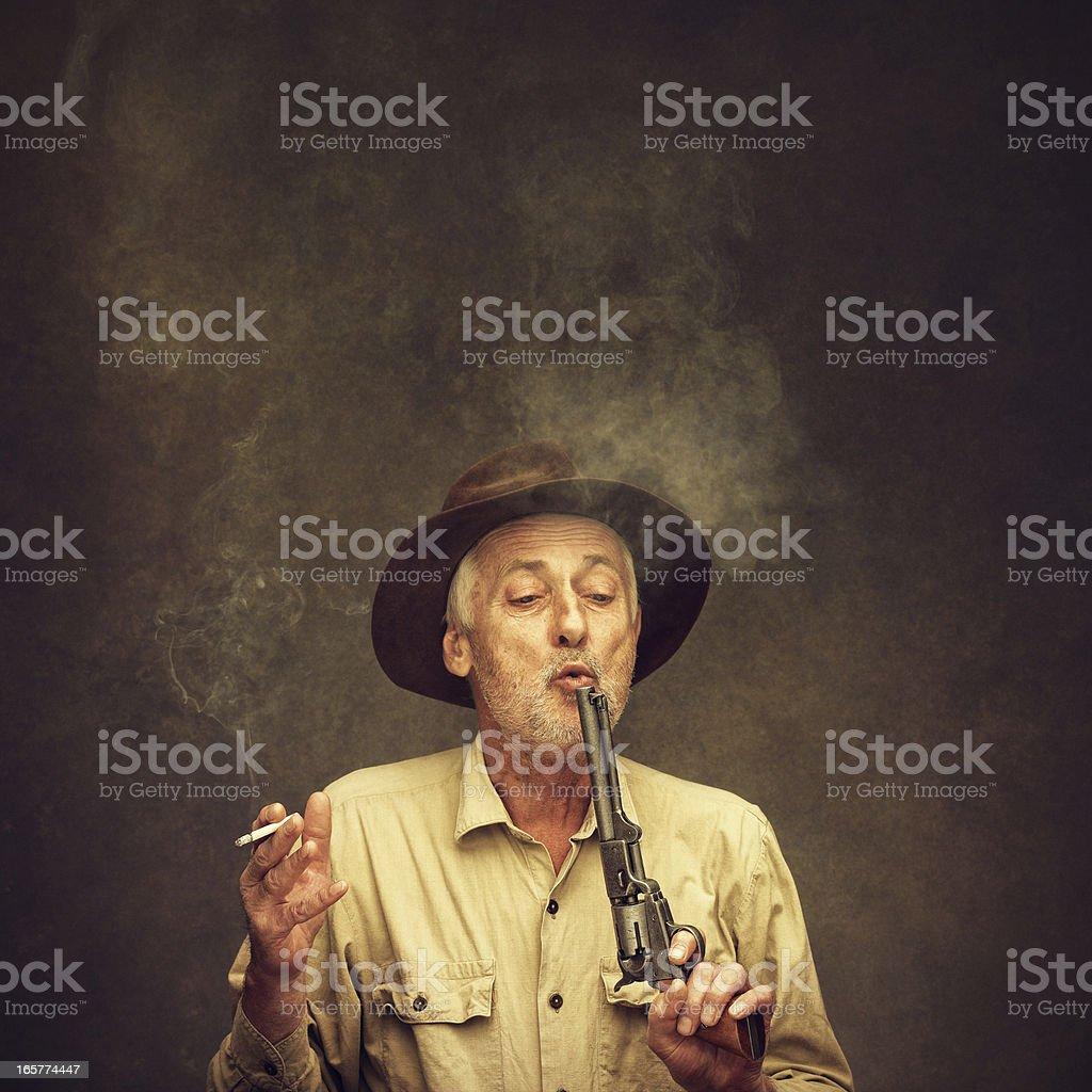 old cowboy blowing the smoke off his gun royalty-free stock photo