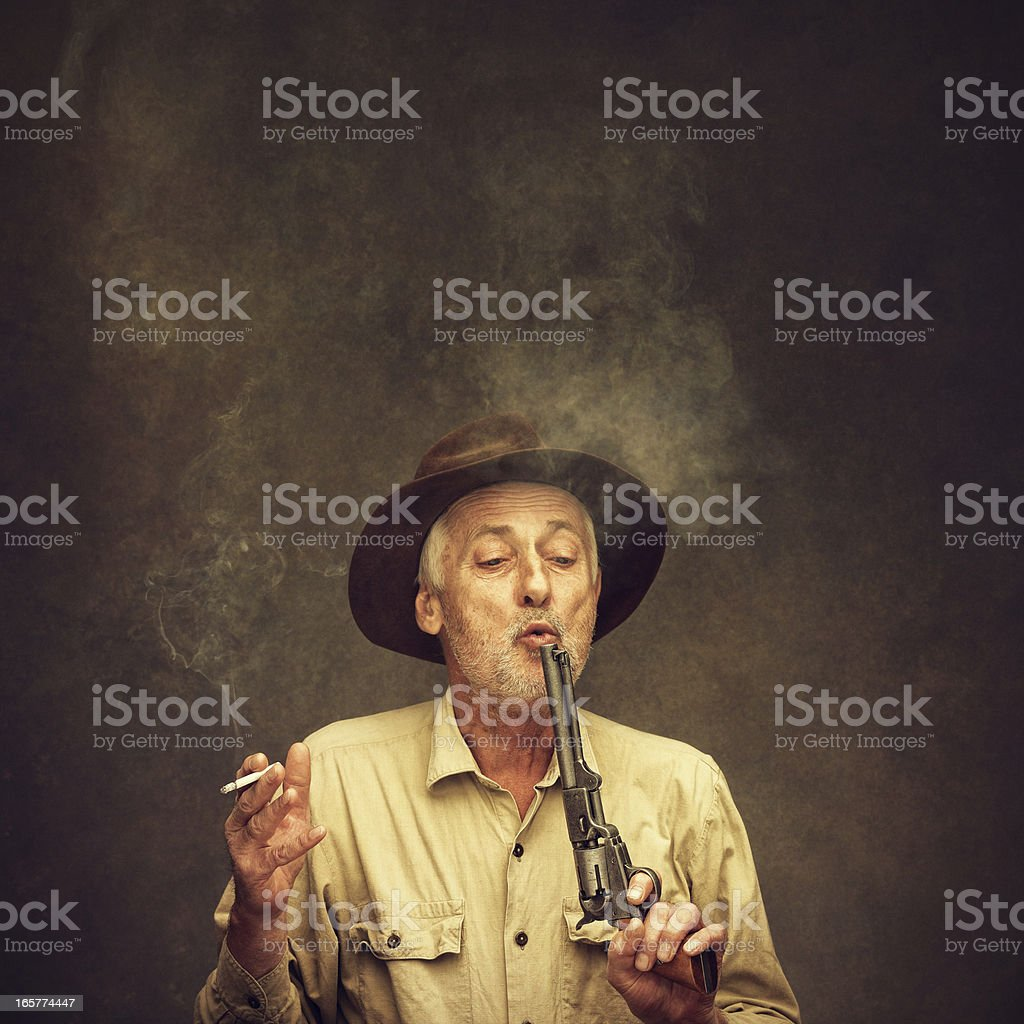 old cowboy blowing the smoke off his gun stock photo