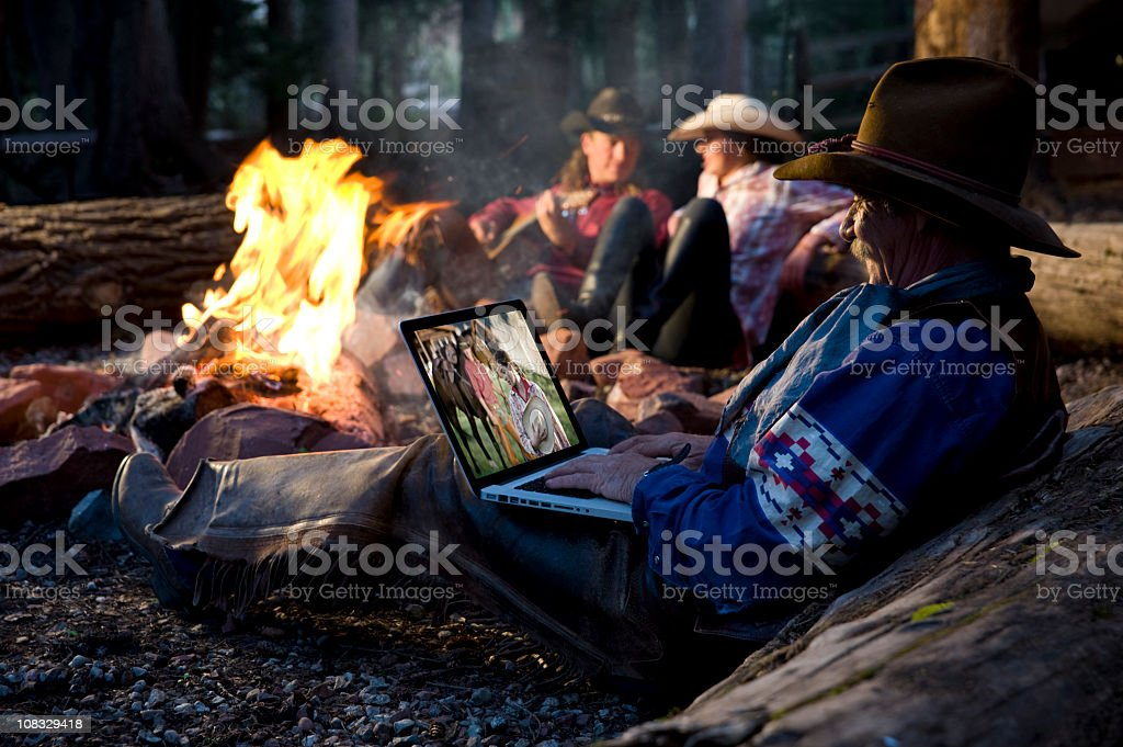 Old cowboy on laptop around camp fire royalty-free stock photo