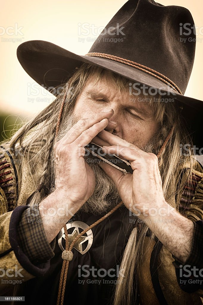 Old cowboy playing harmonica close-up royalty-free stock photo