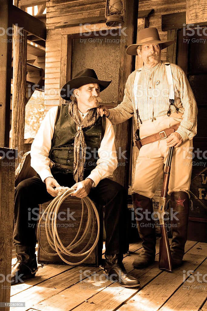 Old cowboys in sepia. Antique, vintage. Wild West town. stock photo