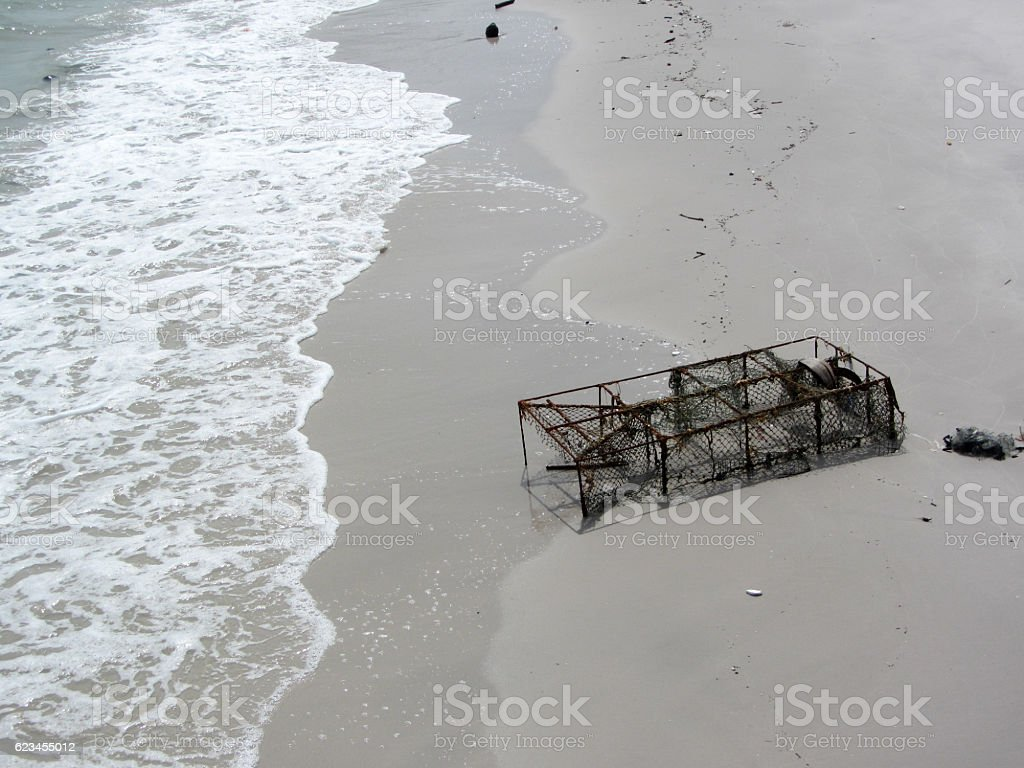 Old Crab trap in sand beach stock photo
