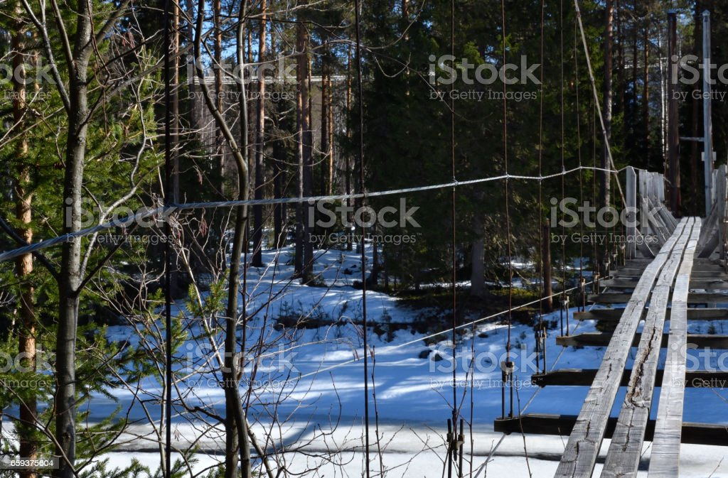 Old cracked  wood suspension bridge for pedestrian over a partly frozen river stock photo