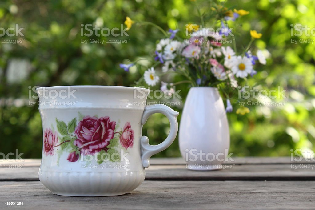 Old cup with flowers stock photo