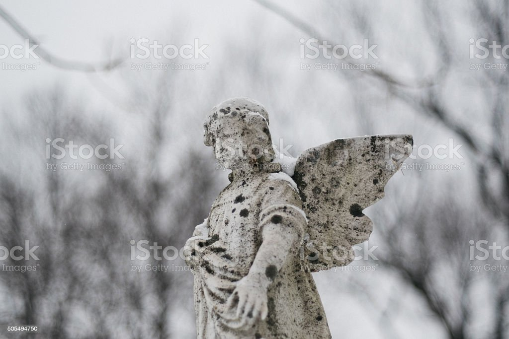 Old cupid statue in a graveyard stock photo