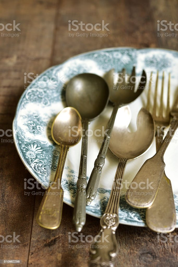Old cutlery on a vintage plate. stock photo